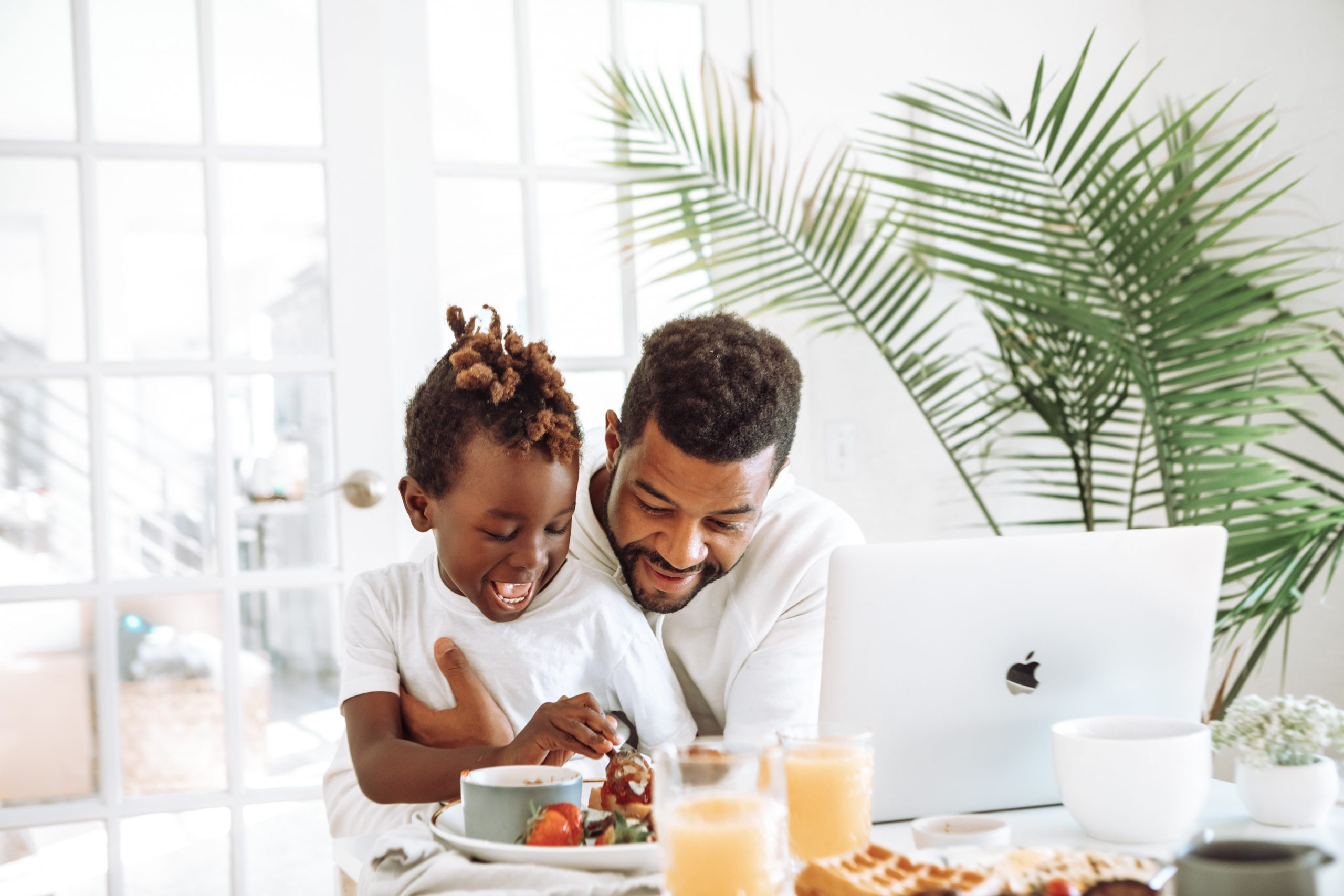 man sitting with son at breakfast table