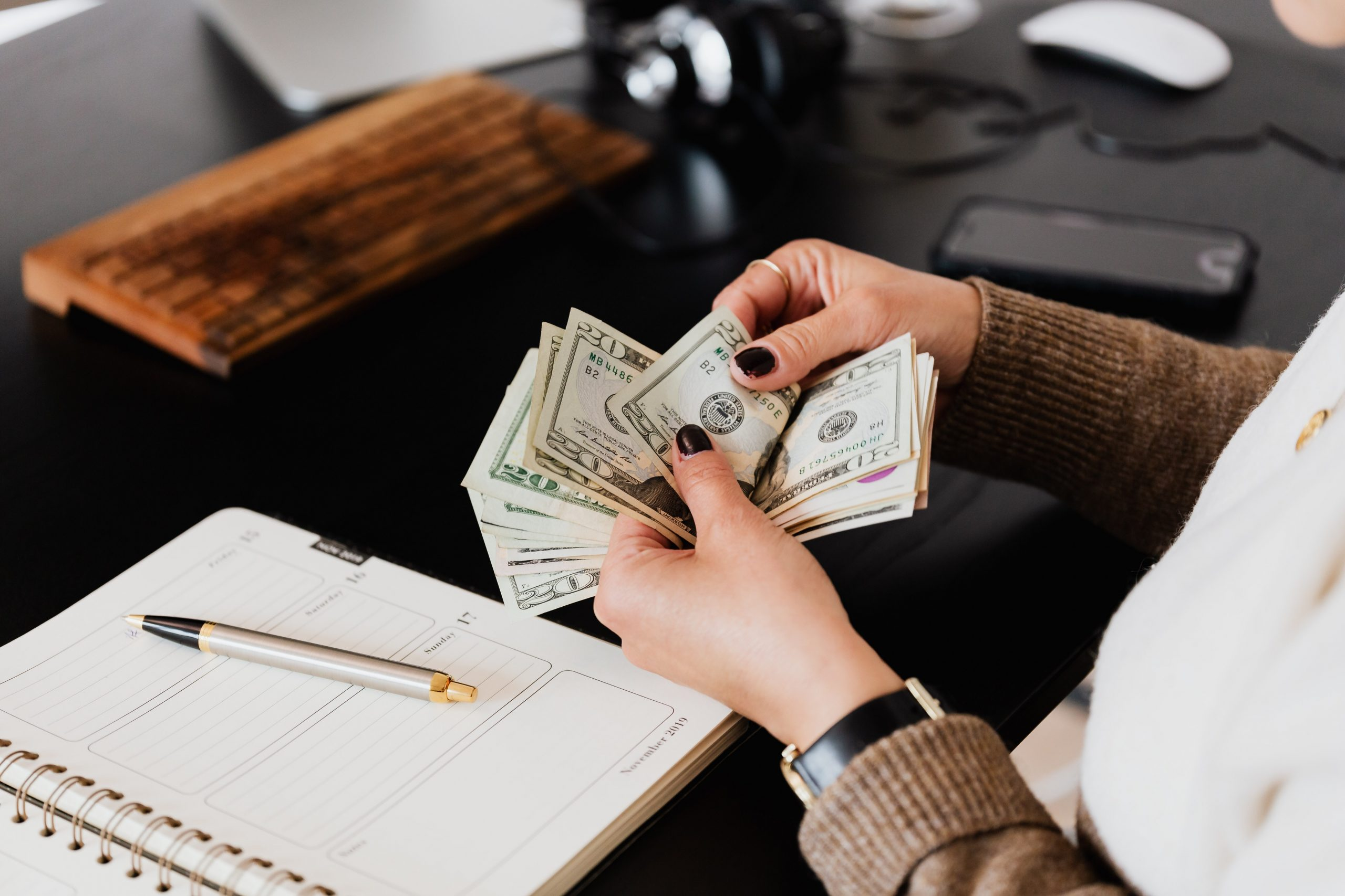 Woman counting cash at her desk