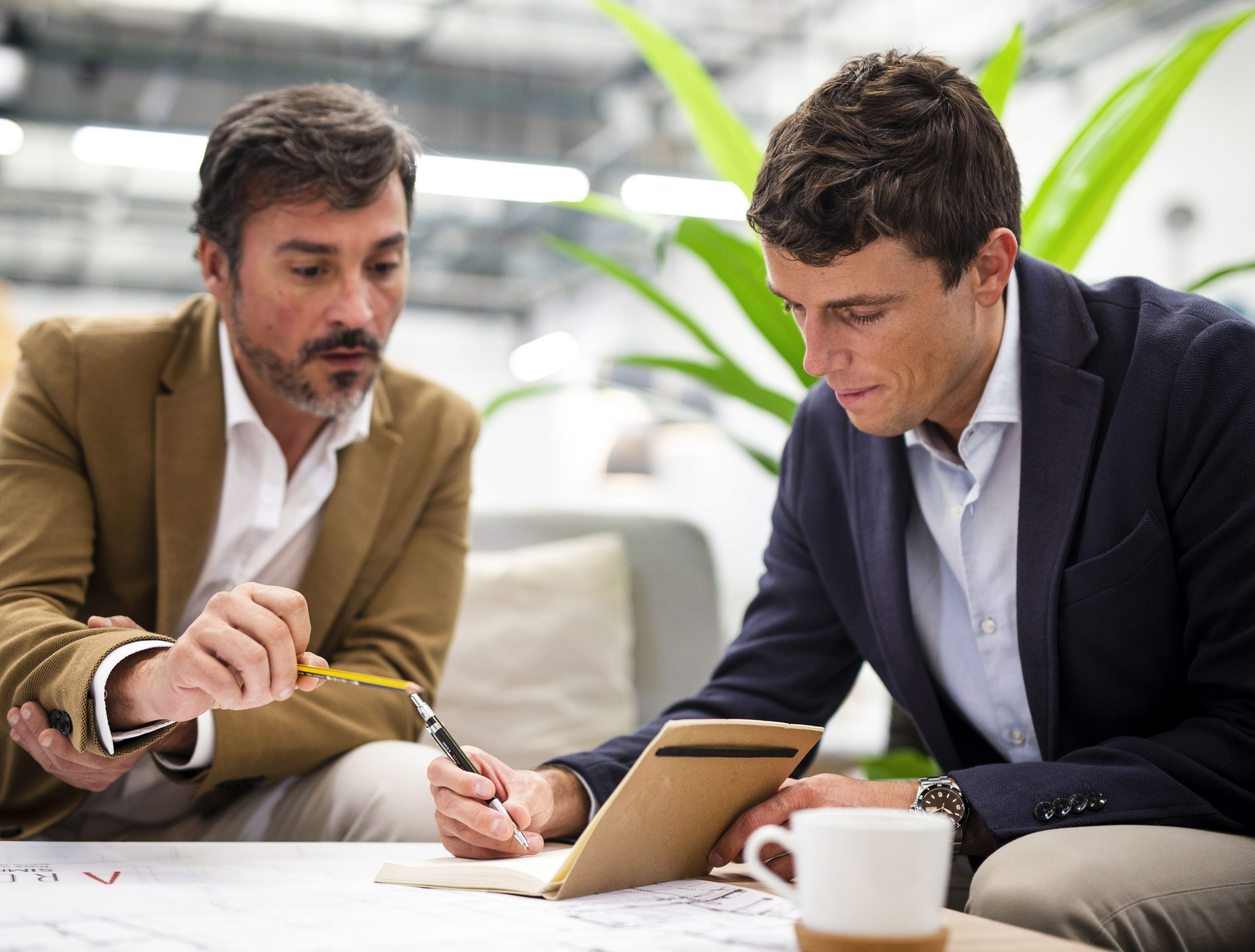 younger businessman taking notes with older businessman