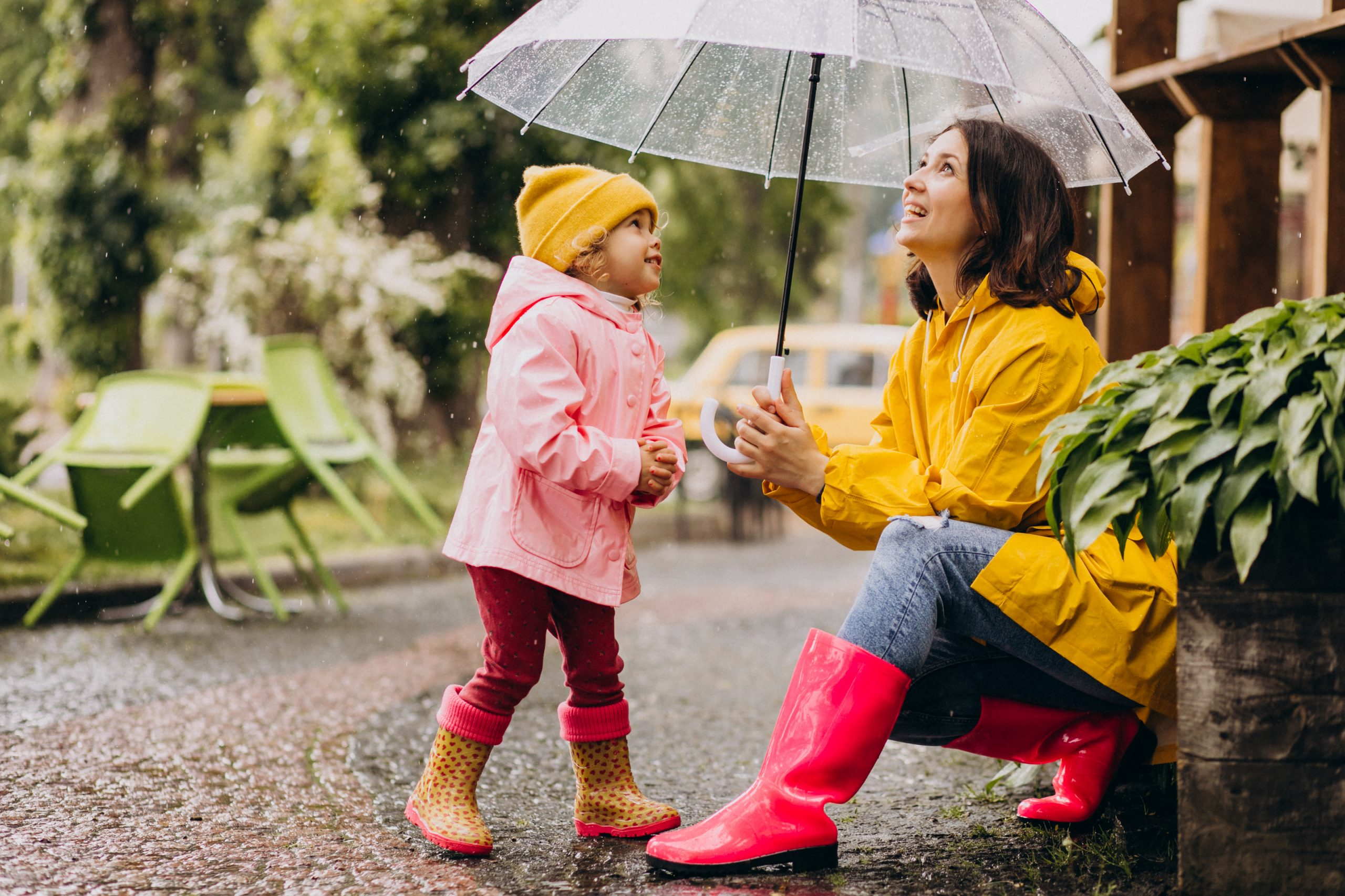 Mother with daughter playing in the rain