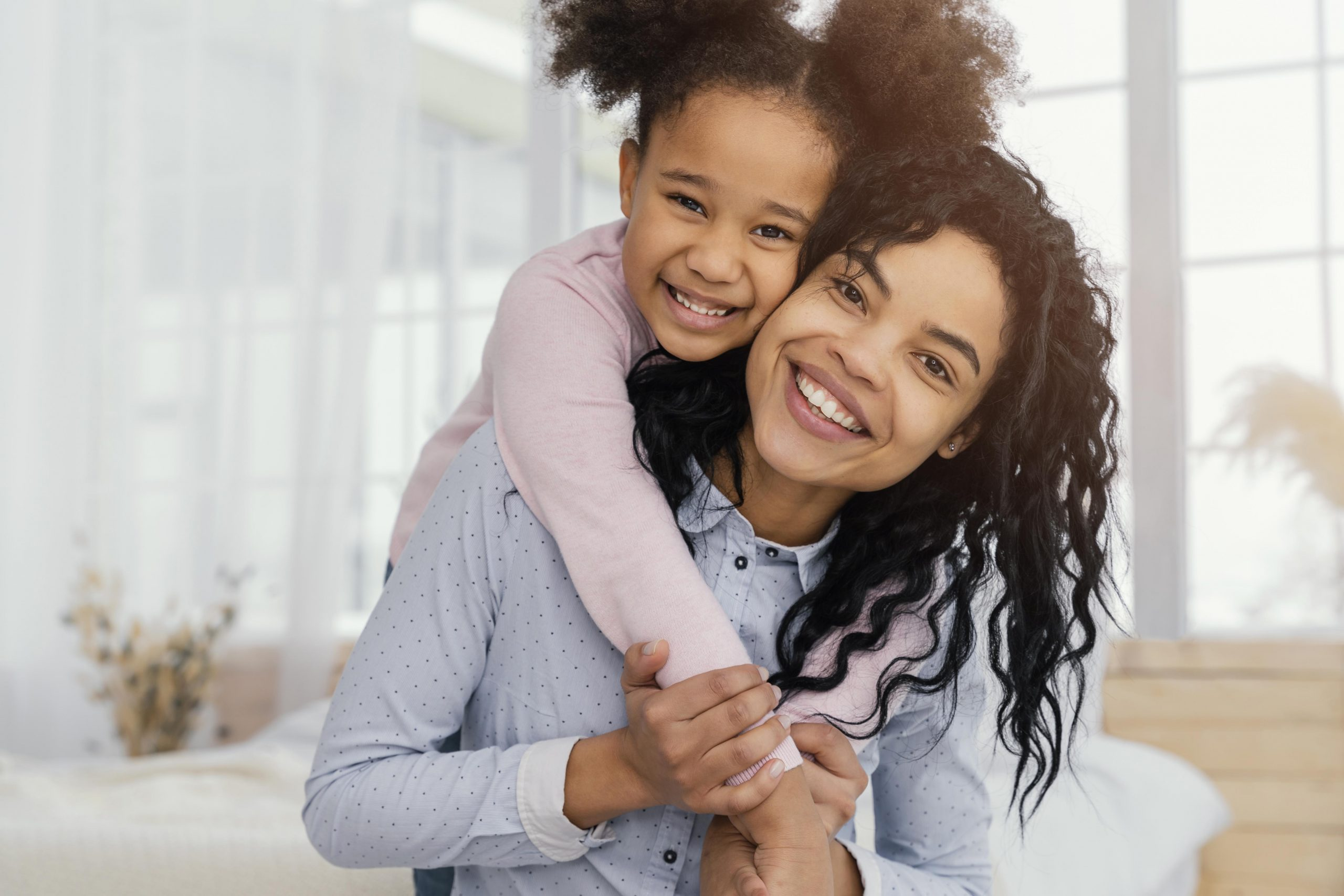woman holding child across her shoulders