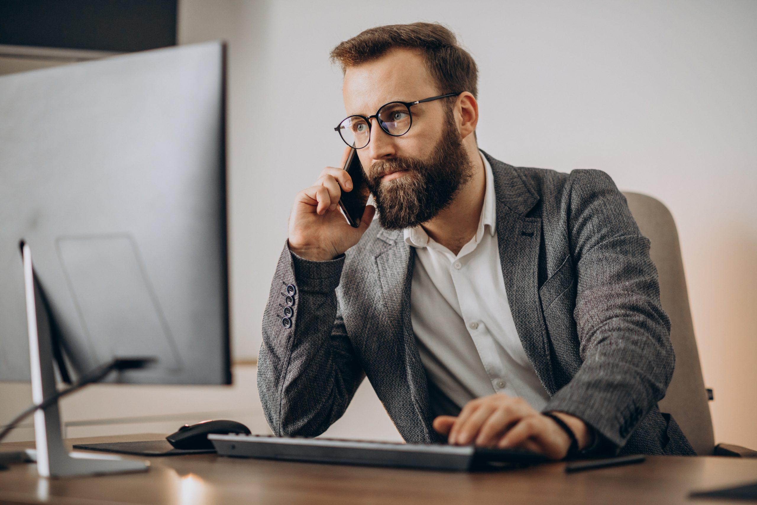 Business talking on phone and working simultaneously