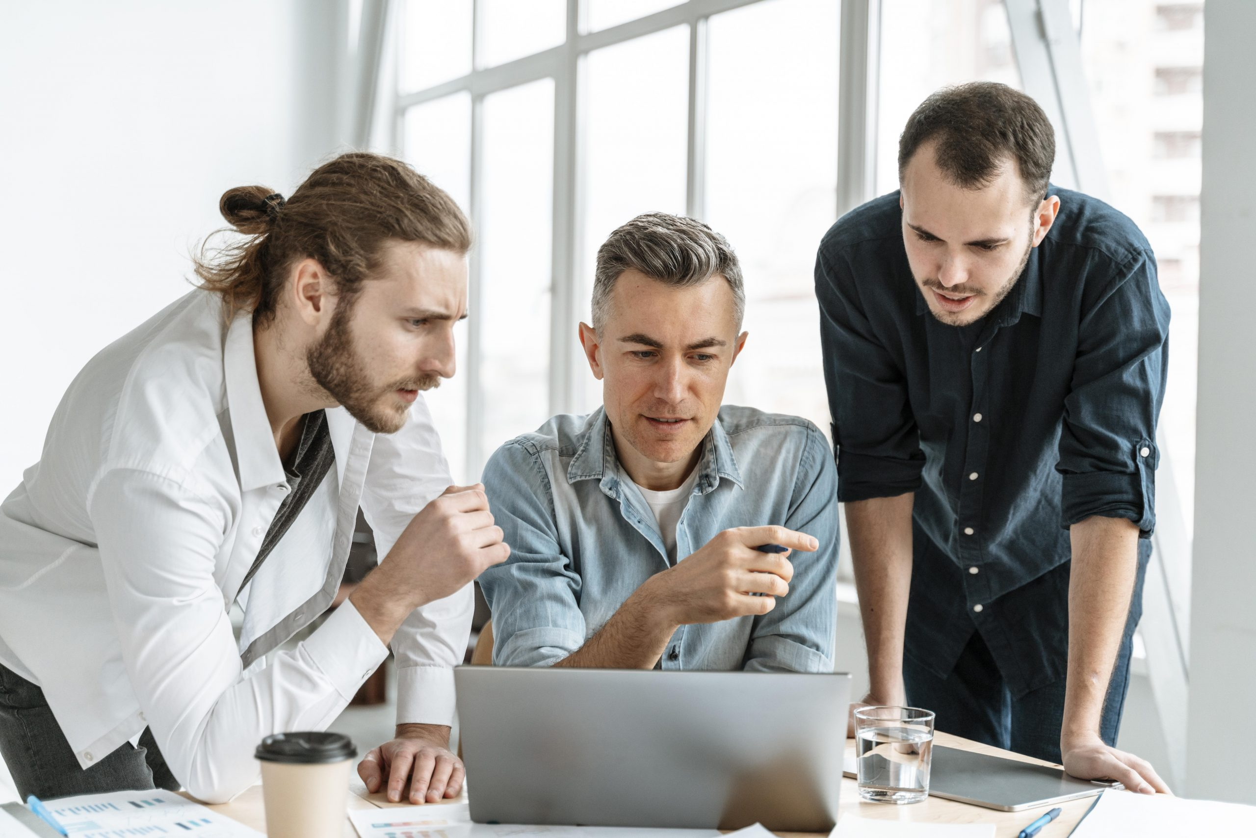 Three men meeting in conference room to talk about business plan